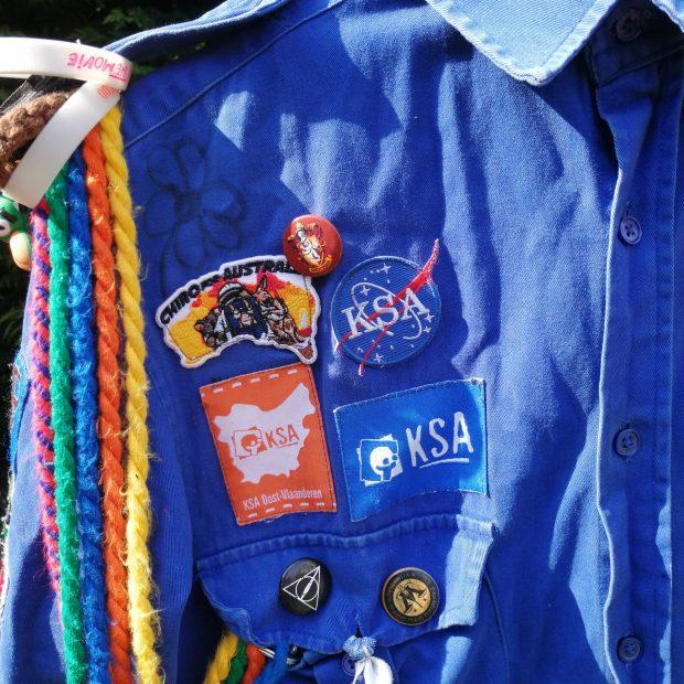 Het blauwe schildje van KSA Nationaal en het oranje schildje van KSA Oost-Vlaanderen komen boven het rechterborstzakje.