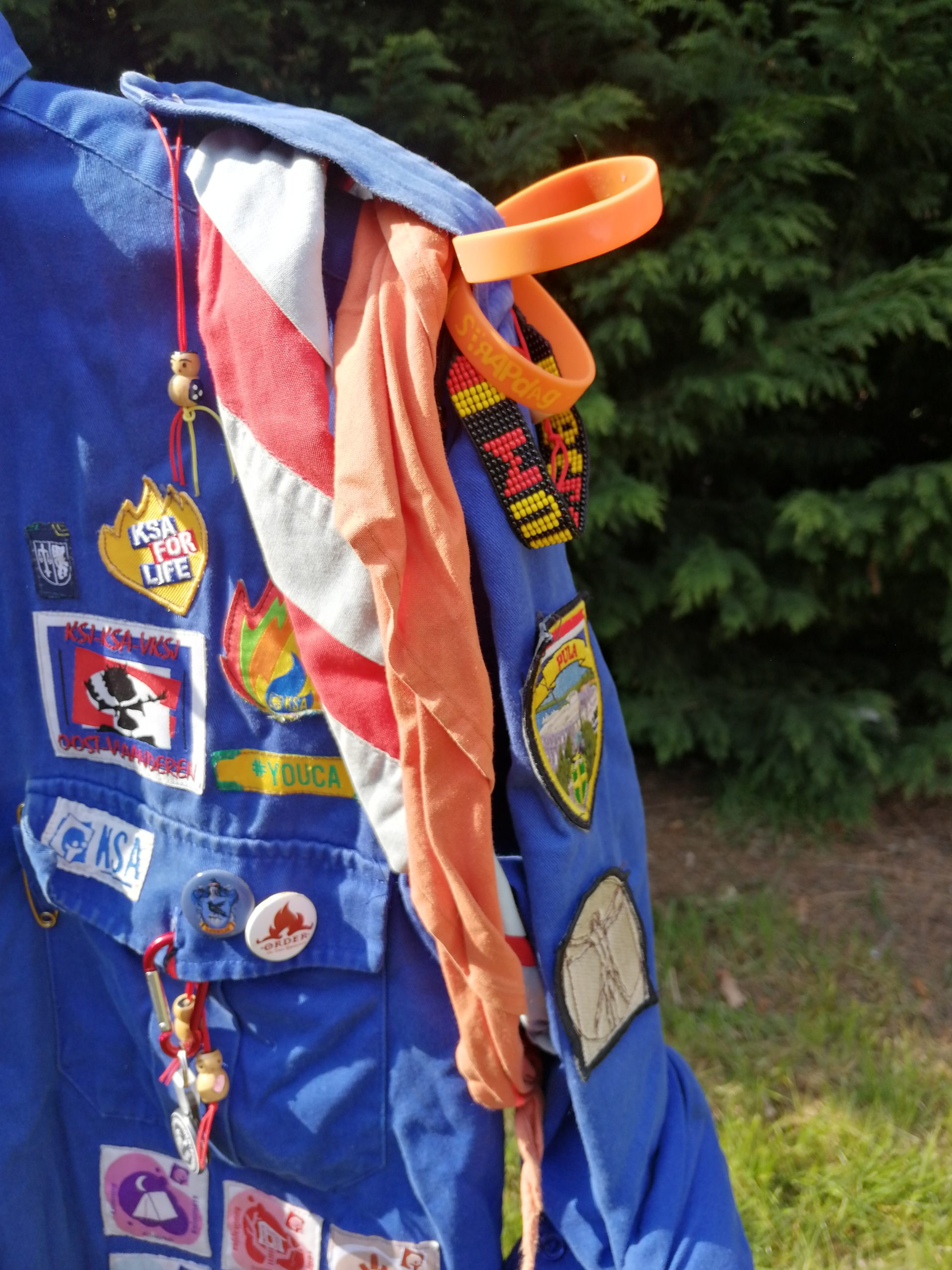 Het oranje sjaaltje komt opgerold om de linkermouw.